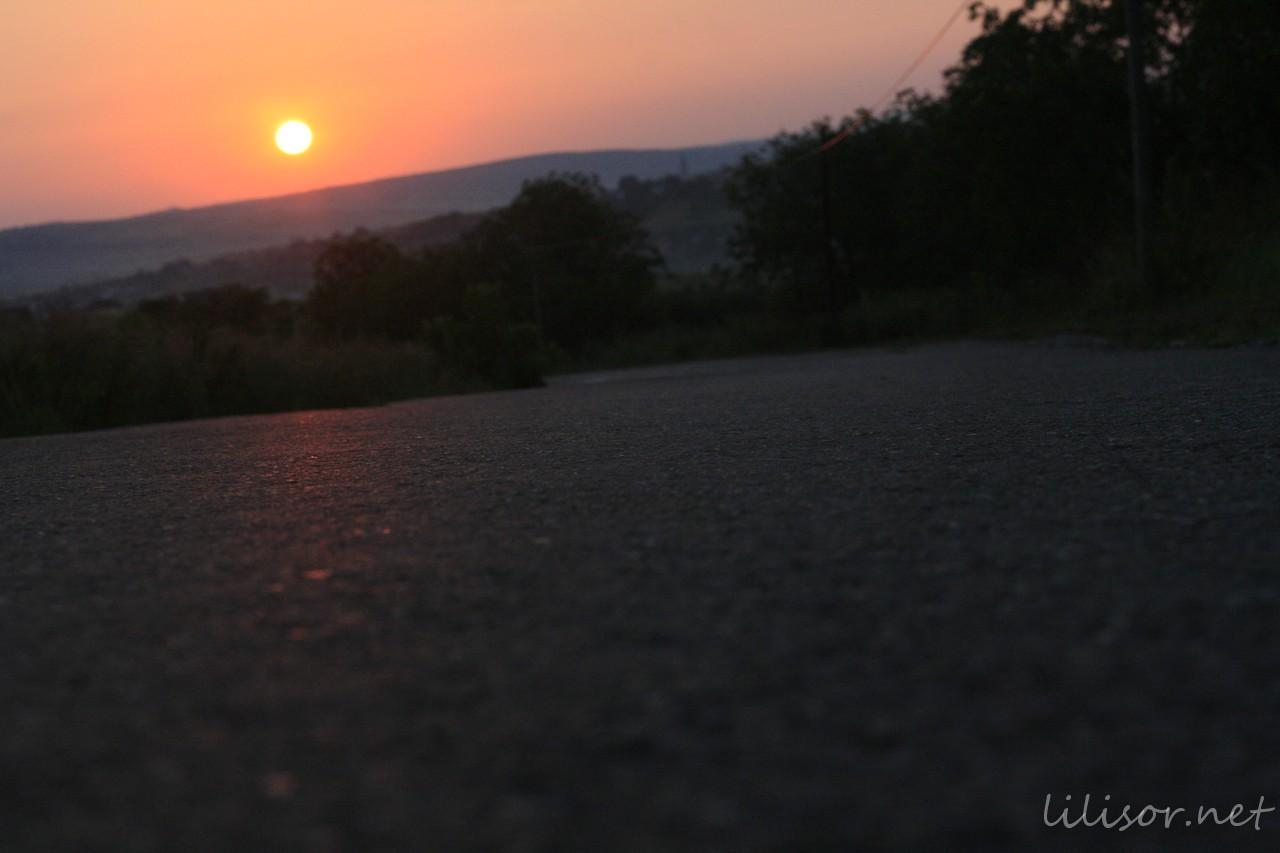 raza de soare oglindindu-se pe șosea